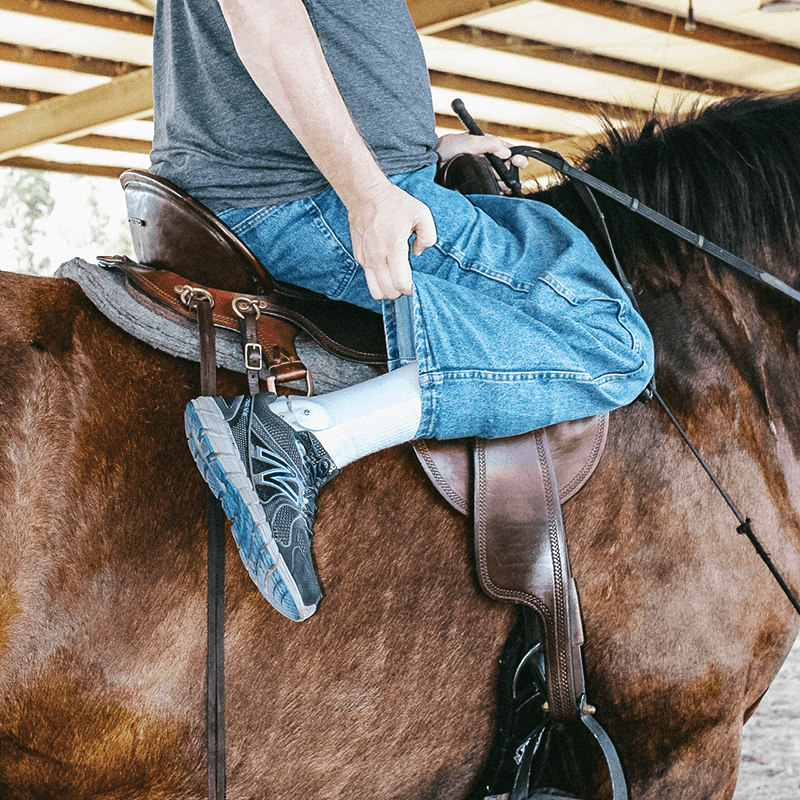 man with prosthetic leg riding a horse