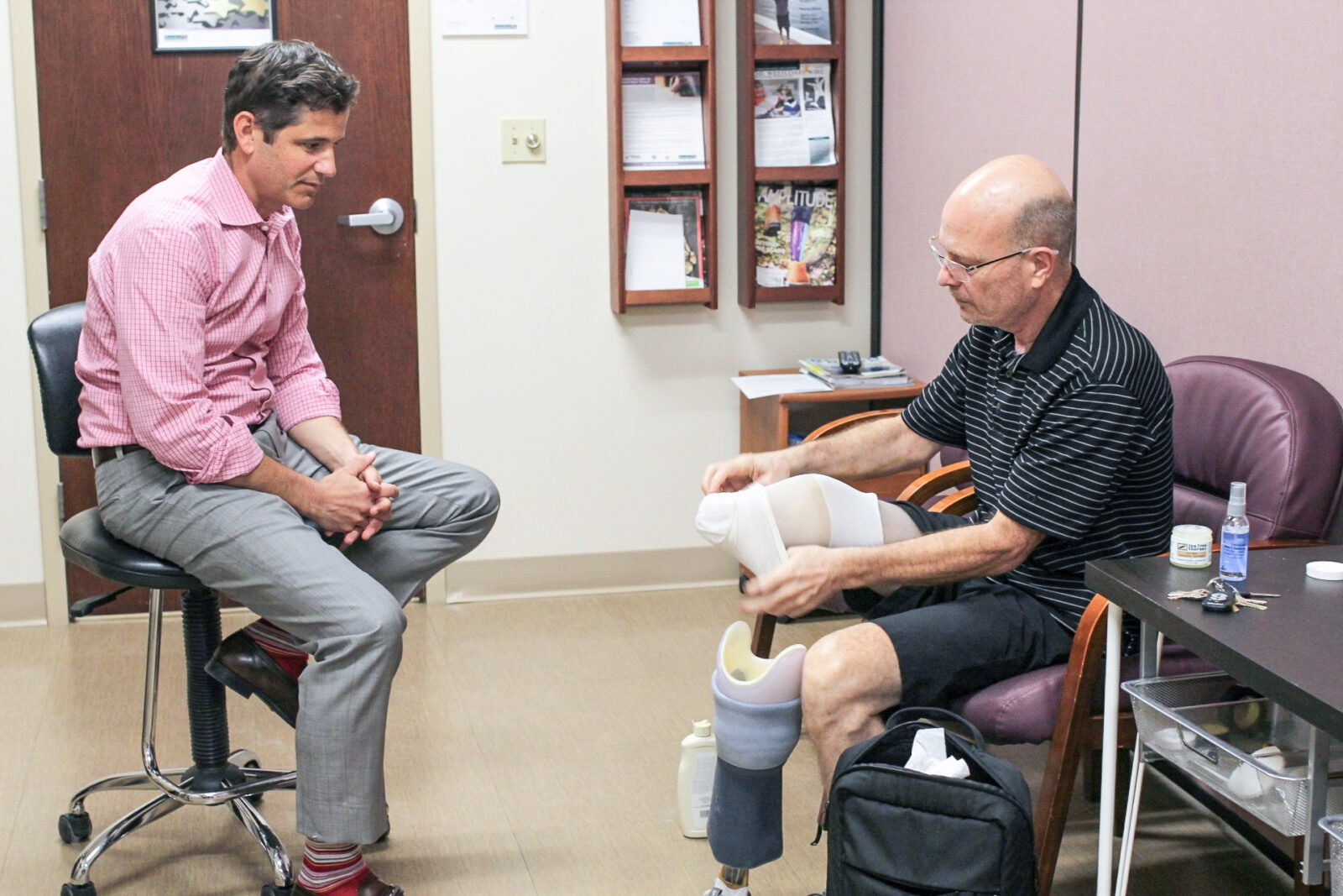 Leg Amputee putting on Prosthetic Leg with prosthetist