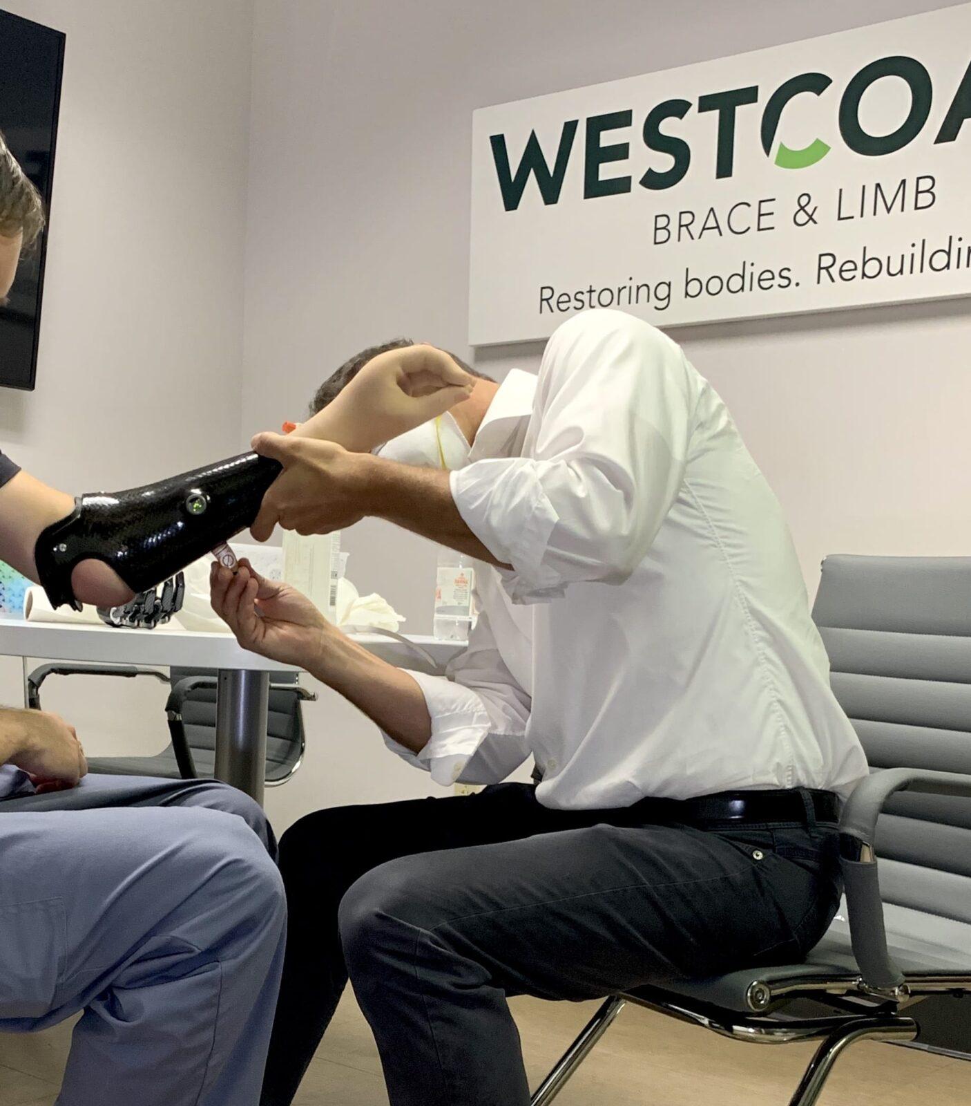Prosthetist adjusting TMR patient's myoelectric prosthetic arm