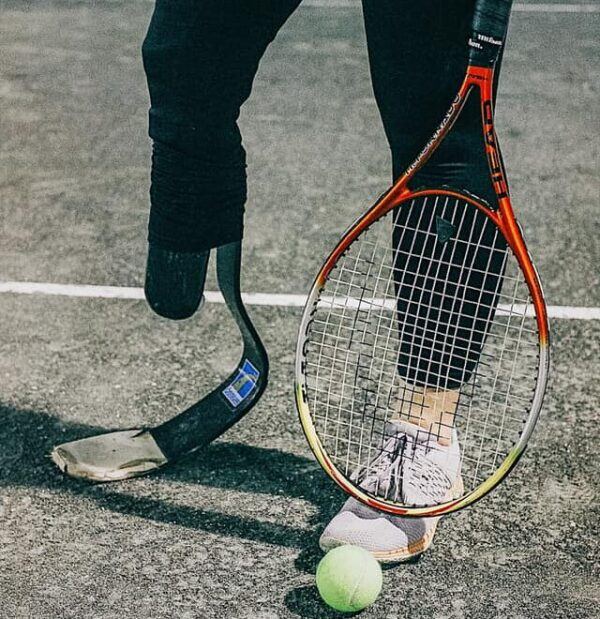 female amputee with running leg socket holding tennis racket