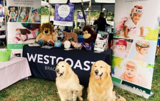 2 golden retrievers, one with a prosthetic leg, in front of WCBL table at High Risk Hope Tot Trot