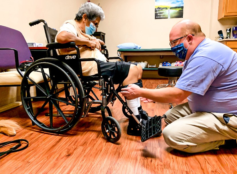 Male orthotist fitting leg brace on woman in wheelchair