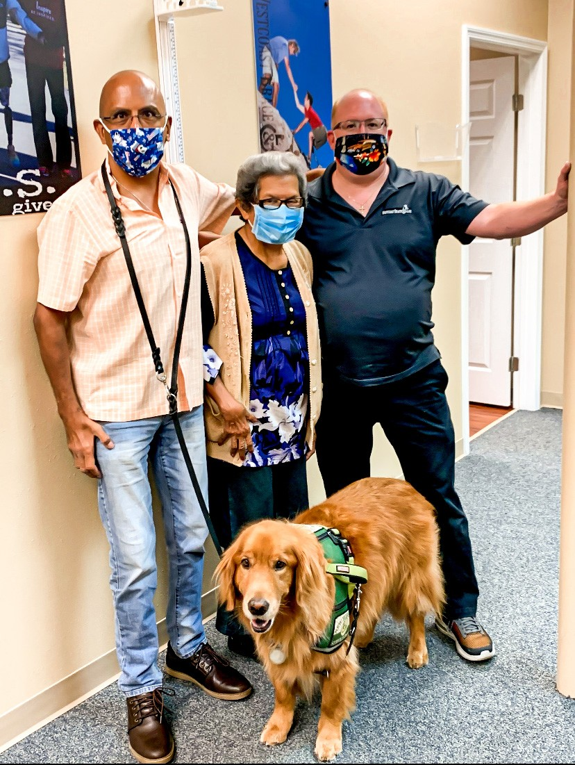 man, woman, standing with orthotist and service dog